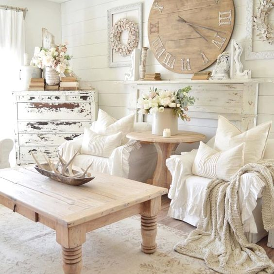 a neutral shabby chic living room with white walls, a shabby sideboard, a wooden clock and a table and some textiles