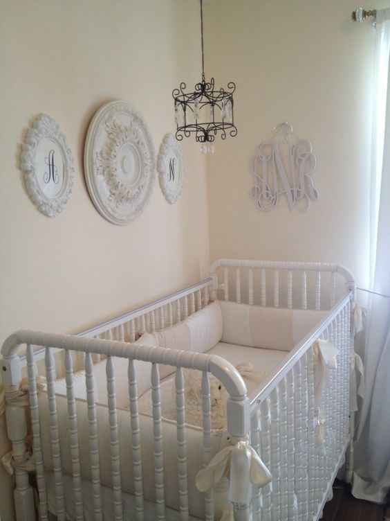 a neutral shabby chic nursery with pastel walls, white vintage furniture, a gallery wall of decorative plates and a small chandelier over the bed