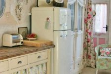 a neutral shabby chic space with refined vintage furniture, floral curtains instead of doors, floral textiles and a wall sconce