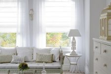 a neutral vintage room with white Roman shades and white semi sheer curtains is a very chic and stylish space that wows