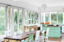 a pastel-infused shabby chic kitchen with aqua furniture, a shabby table, mismatching chairs and floral prints