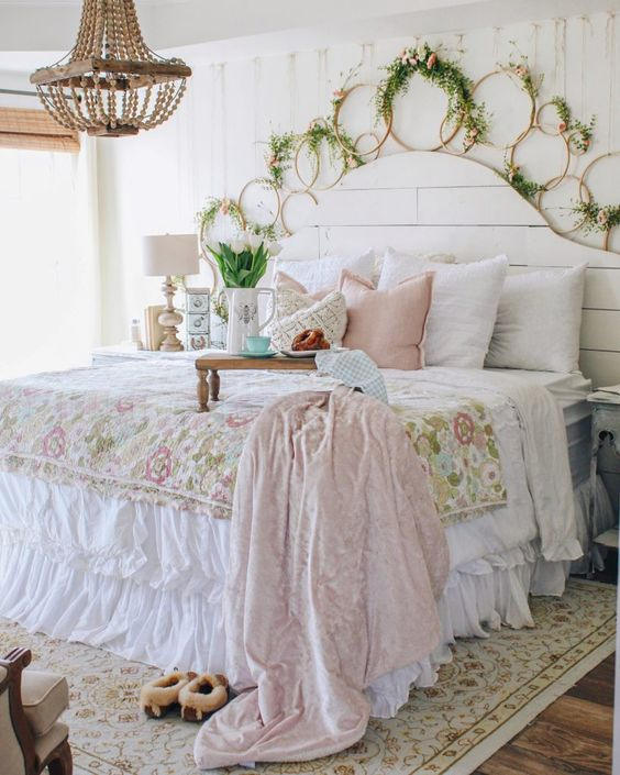 a pastel shabby chic bedroom with a white beadboard bed, pastel and floral bedding, lots of hoops with blooms, a bead chandelier