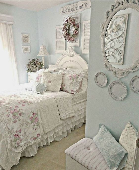 a pastel shabby chic bedroom with blue walls, shutters, plates, a mirror, floral bedding and a gallery wall