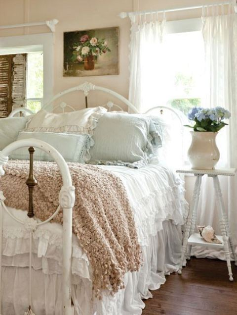 a pastel shabby chic bedroom with peachy walls, a white metal bed, pastel bedding, blooms and vintage shutters