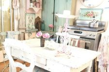 a pastel shabby chic kitchen with pastel blue and pink cabinets, a white table, floral chairs and linens plus a couple of crystal chandeliers