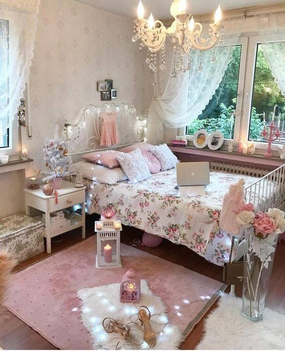 a pink and white shabby chic bedroom with a forged bed, white furniture, pink and floral bedding, candle lanterns and a crystal chandelier