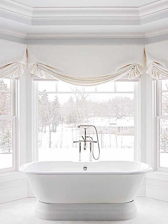 a refined bathroom with a view with neutral Roman shades that makes the space private whenever it's needed
