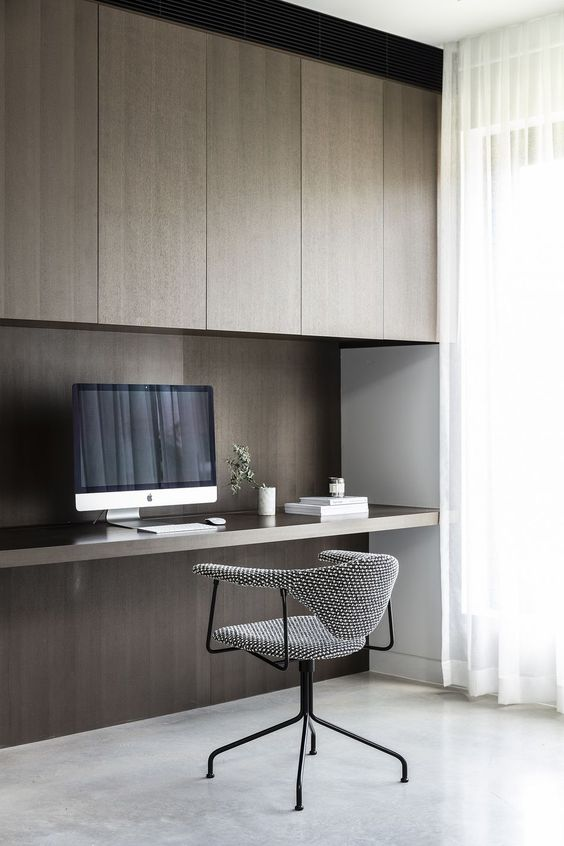 a refined minimalist home office with dark stained sleek cabinets, a built-in desk, a grey chair and a large window for more natural light