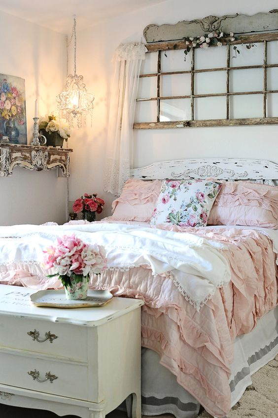 a refined shabby chic bedroom with an old window frame, white shabby furniture, a crystal pendant lamp and pink and floral bedding