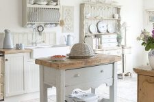 a romantic neutral shabby chic kitchen with beadboard cabinets, an off-white kitchen island and refined open storage units