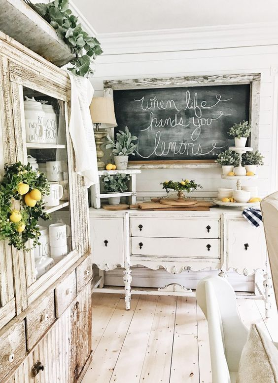 a romantic neutral shabby chic kitchen with refined furniture, a chalkboard, potted greenery and lemons for a touch of color