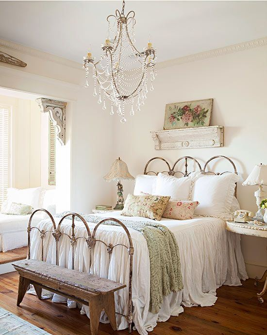 a romantic shabby chic bedroom with a forged bed, a crystal chandelier, chic lamps and artworks