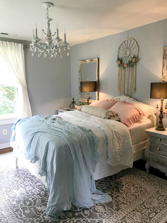 a romantic shabby chic bedroom with pastel blue walls, a dream catcher, refined furniture, a crystal chandelier and ruffled bedding