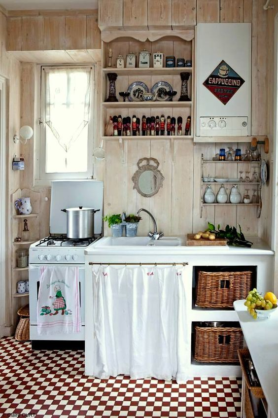 a rustic shabby chic kitchen in neutrals, with a white cabinet with baskets, a curtain over a cabinet, open storage units and vintage linens