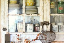 a rustic shabby chic kitchen in neutrals, with glass cabinets, beadboard walls, vintage pottery and porcelain for beautiful decor