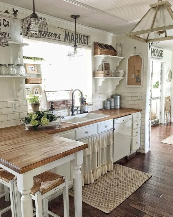 a rustic shabby chic kitchen with a ruffled curtain on a cabinet, metal and wooden pendant lamps and green blooms