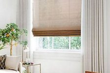 a semi sheer burlap Roman shade paired with creamy curtains makes the window look cooler and allows to keep the space private when needed