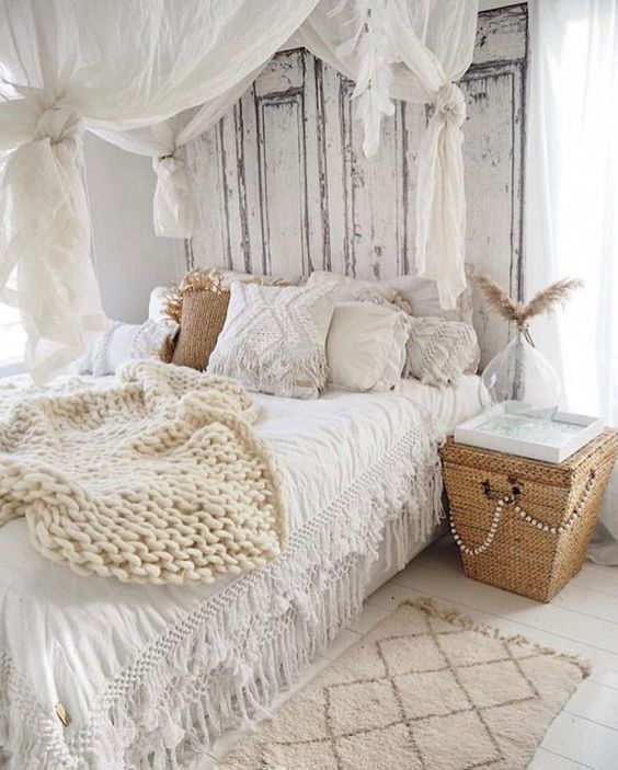 a shabby boho bedroom with shabby doors instead of a headboard, a canopy, crochet and lace pillows, a basket nightstand
