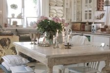 a shabby chic French country kitchen in neutrals, with a black bench, a crystal chandelier and touches of stained wood
