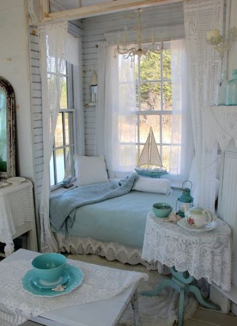 a shabby chic bedroom in white and pastel blue, with a bed in an alcove, with pastel blue bedding and lace and a vintage chandelier