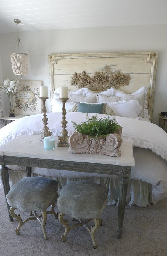 a shabby chic bedroom with a neutral wooden bed, a table and grey stools, a bed chandelier and candles