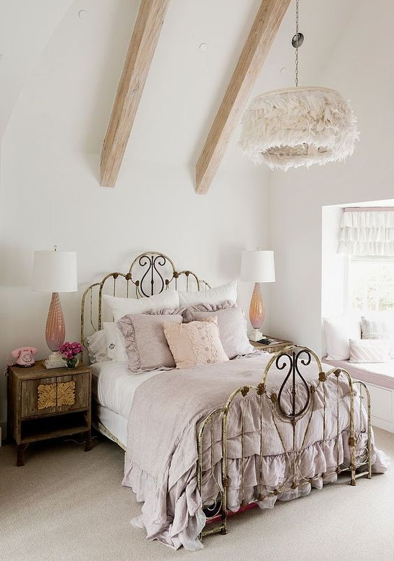 a shabby chic bedroom with a shabby forged bed, stained wooden furniture, a fluffy pendant lamp and pastel bedding