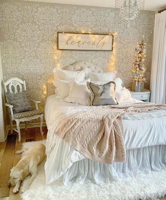 a shabby chic bedroom with a wallpaper wall, refined neutral furniture, ruffle textiles, lights and a crystal chandelier