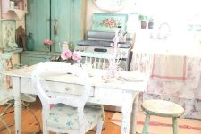 a shabby chic kitchen with neutral shabby furniture, floral textiles and linens, an aqua sideboard and a pink shelving unit