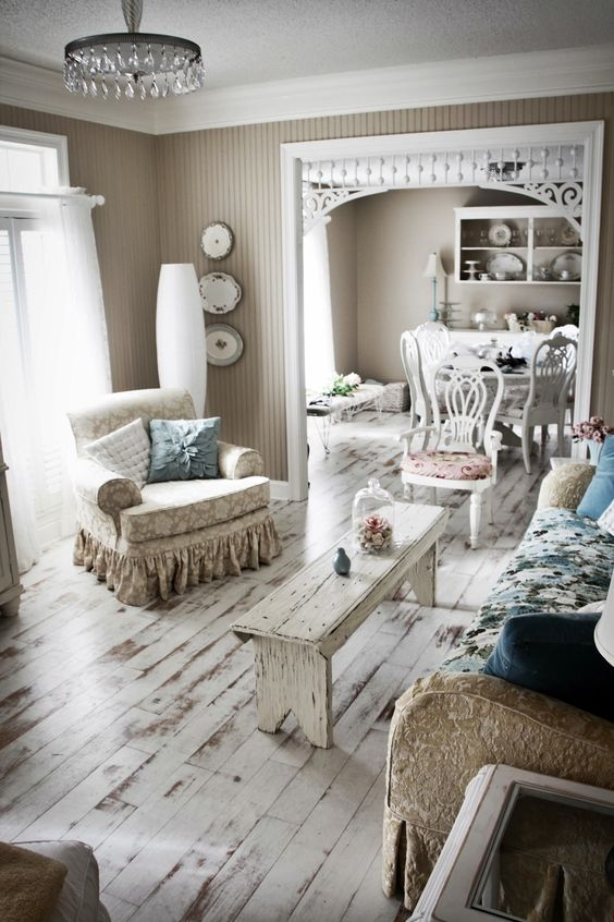 a shabby chic living room with a blue floral sofa, printed chairs and a white bench, a crystal chandelier and pastel pillows