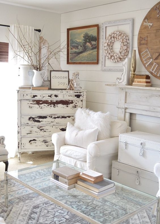 a shabby chic living room with a faux fireplace, white chests, white chairs, a shabby sideboard and a glass table