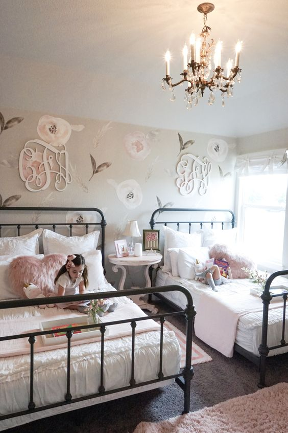 a shabby chic shared bedroom with a floral statement wall, metal beds, pink bedding, a refined nightstand and a crystal chandelier