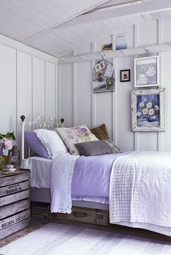 a shabby farmhouse bedroom in white, with a forged bed, a crate nightstand, some vintage suitcases and a gallery wall