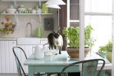 a simple shabby chic kitchen with white beadboard cabinets, light blue shabby furniture, green touches and potted greenery