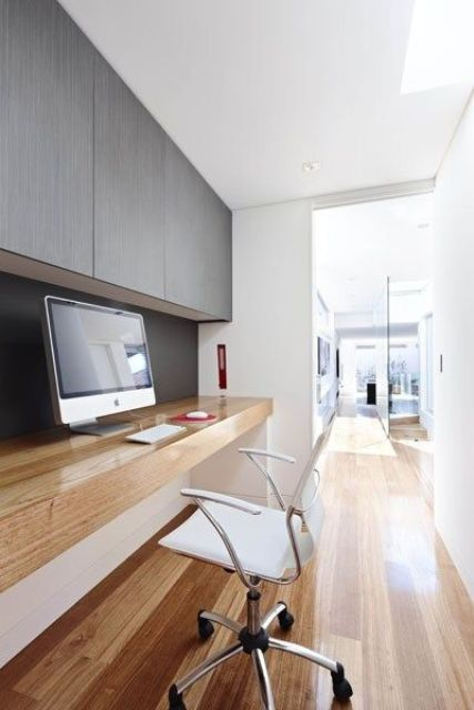 a sleek minimalist home office space with a sleek storage unit, a built in desk, a white chair and a PC are all you need for working