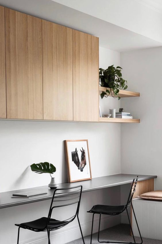a sleek minimalsit home office with a sleek storage unit and built-in shelves, a floating desk, black chairs and a windowsill bench