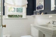 a small bathroom with black and white walls, white appliances, art and a white Roman shade that brings a traditional feel to it