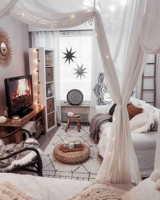 a small boho living room accented with mosquito net curtains and lights interwoven