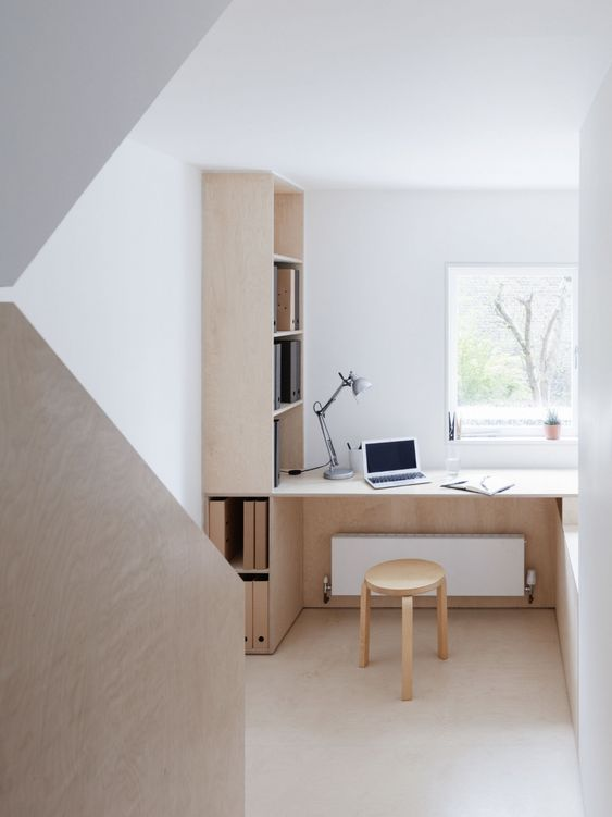 a small minimalist home office nook with a view, a built-in plywood storage unit, a built-in desk and a stool is chic and comfortable