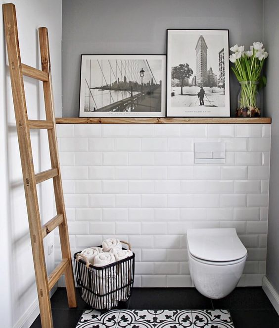 a small monochromatic powder room accented with a wooden ladder and a ledge with artworks and blooms looks warmer and cooler
