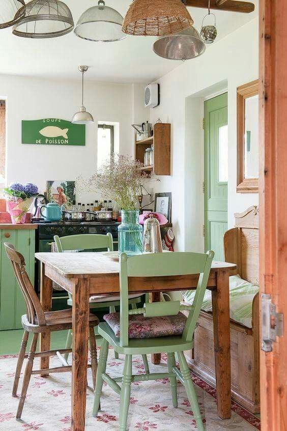 a small shabby chic kitchen with green furniture, metal and woven lamps, a wooden table and storage units and blooms