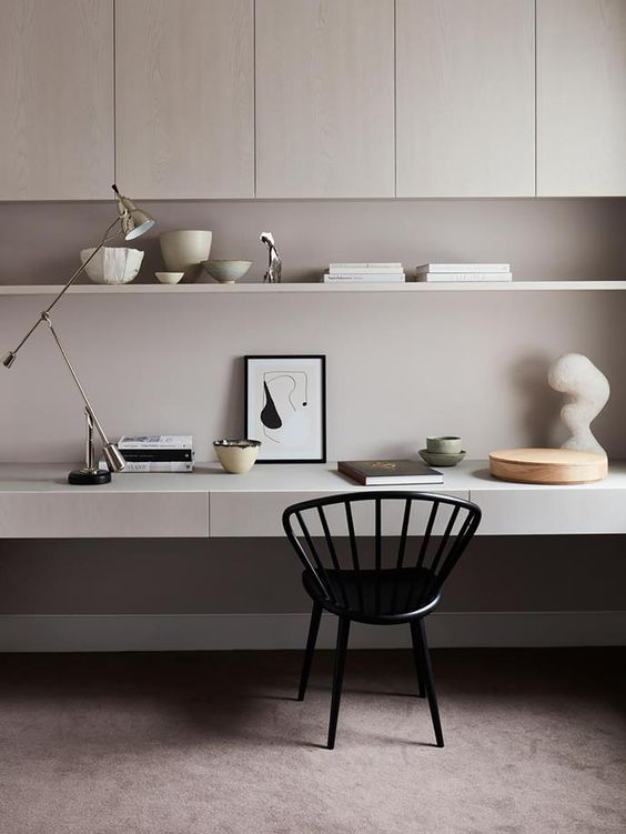 a sophisticated grey minimalist home office with sleek storage cabinets, an open shelf, a built-in desk and a black chair plus some lamps