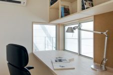 a stylish and cool minimalist home office with an open shelving unit, a desk, a black chair and small windows with a view