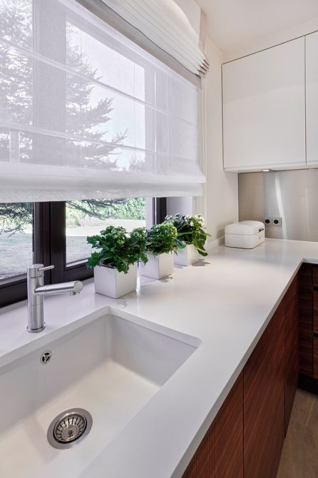 a stylish contemporary kitchen with semi sheer Roman shades that add coziness and don't block the views