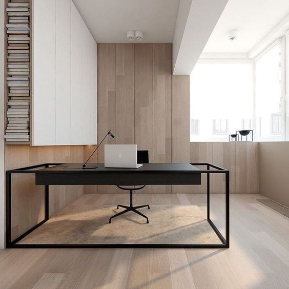 a stylish minimalist home office clad with light stained wood, with a large sleek white storage unit, a black desk and a glazed wall