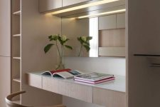 a stylish minimalist home office nook with light stained plywood furniture, a built-in desk and lights, a comfortable chair and a mirror