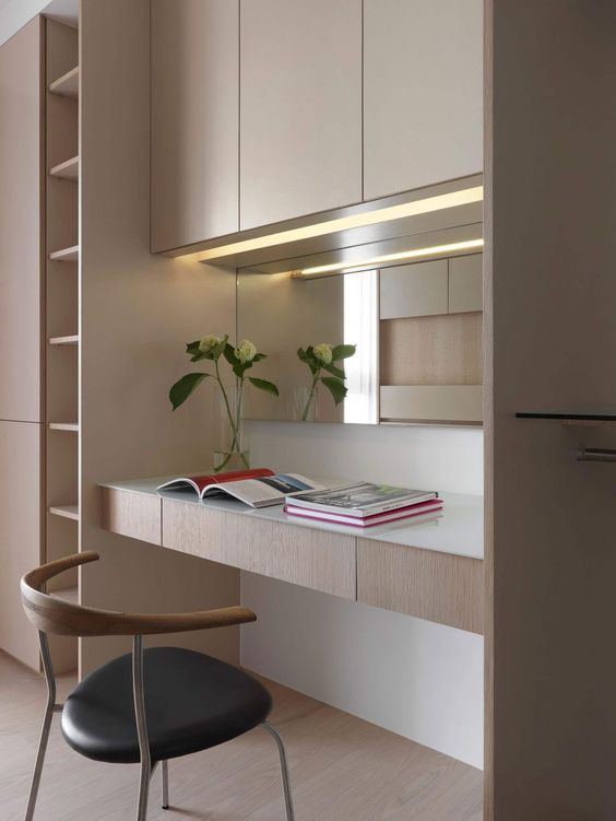 a stylish minimalist home office nook with light stained plywood furniture, a built in desk and lights, a comfortable chair and a mirror