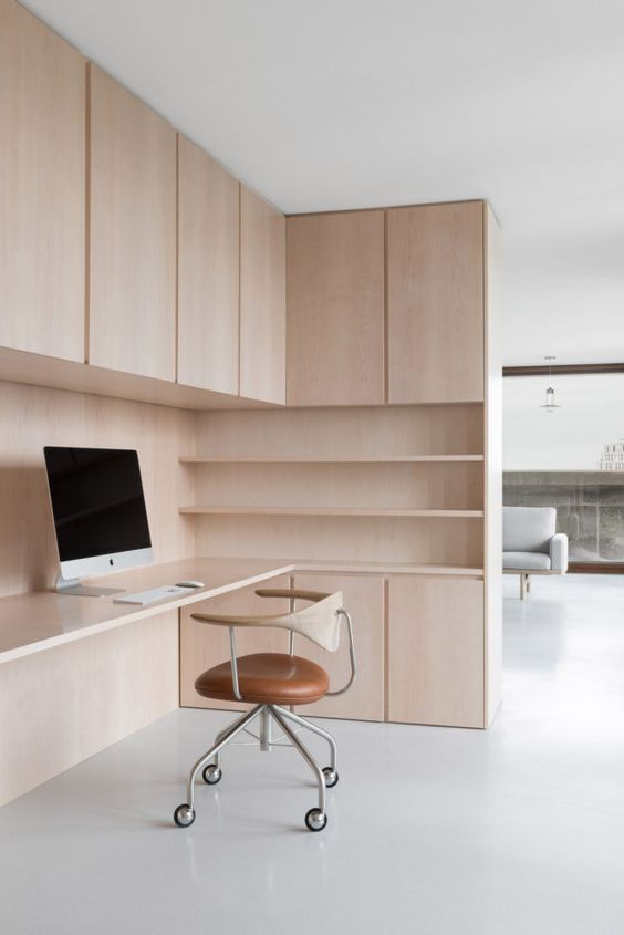 a stylish minimalist home office with light stained plywood, with storage units and open shelves, a cool plywood and leather chair