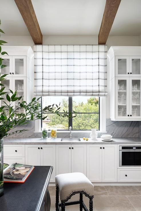 a subtle grey and white plaid Roman shade is a cool accent and addition of a print to the farmhouse space is lovely