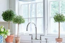a traditional kitchen with white and blue Roman shades that add interest and coziness to the space