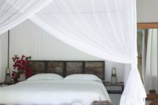 a tropical bedroom with a pallet bed and bench plus mosquito net canopies and curtains